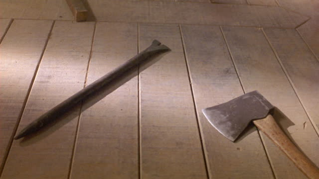 medium angle of metal axe with wooden handle and metal pick or stake sitting on wooden floor. mining equipment. tools. - axe stock videos and b-roll footage