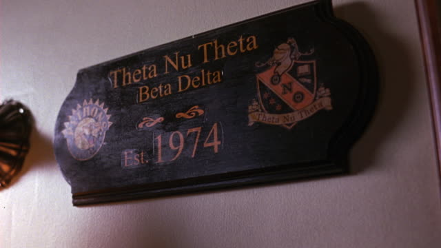 medium angle of wall in fraternity house or frat house. plaque commemorating founding of theta nu theta in 1974. - nu stock videos & royalty-free footage