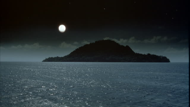 WIDE ANGLE OF SILHOUETTE OF ISLAND AND SURROUNDING OCEAN. SEE FULL MOON AT LEFT.