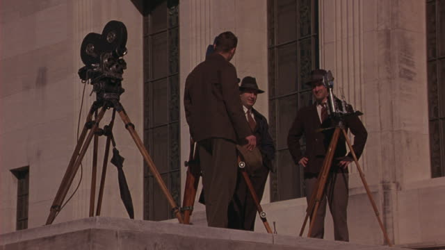 medium angle of reporters with reel to reel film cameras on tripods in front of capitol building in baton rouge, louisiana. government buildings. - kapitol von louisiana stock-videos und b-roll-filmmaterial