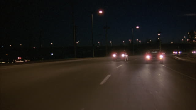 process plate. city traffic on freeway at night. see car pass out of left side of frame, while all other cars remain in shot. - motorway stock videos & royalty-free footage