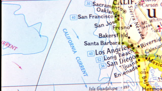 CLOSE ANGLE OF WORLD MAP OR GLOBE. SHOT BEGINS ON HONOLULU HAWAII THEN PANS RIGHT TO SOUTHERN CALIFORNIA COAST. CAMERA PANS DOWN BAJA MEXICO THEN BACK TO HAWAII. SEE LATITUDE AND LONGITUDE LINES ON MAP.