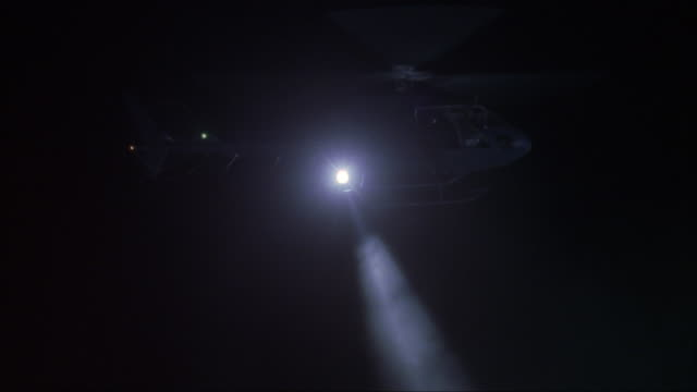 medium angle of stationary helicopter in air with search light pointing downward. - searchlight stock videos & royalty-free footage