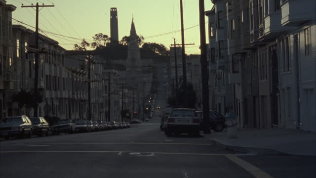 medium angle of city street that slopes uphill to telegraph hill with coit tower at top center. - north beach san francisco stock videos and b-roll footage