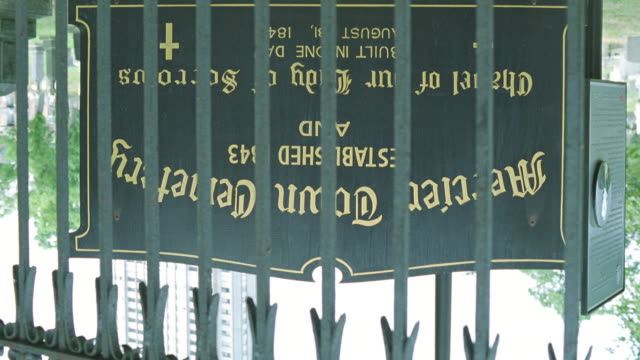 pan down from upside down shot of gate or fence to mercier town cemetery sign in front of graveyard. established 1843 and chapel of our lady of sorrows on sign. pan right along iron gate - https stock videos & royalty-free footage