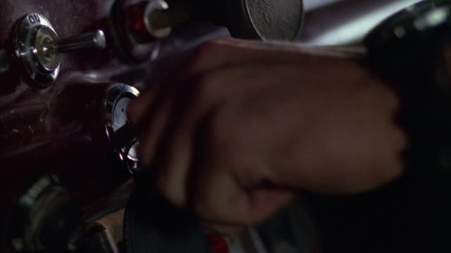 close angle of keys in ignition of car. see hand reach and turn keys to right, probably starting car. see red paneling or dashboard in background. see key chain hanging from key. - 点火装置点の映像素材/bロール