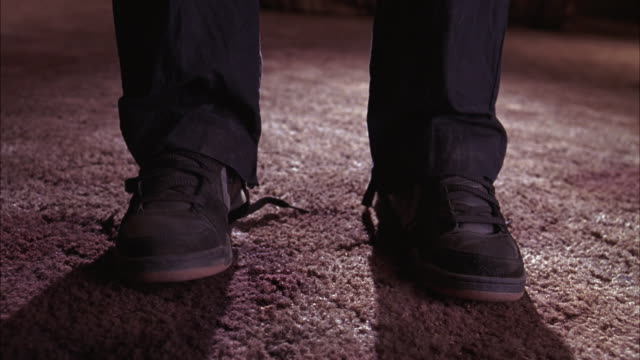medium angle of man's shoes and legs standing on carpet in lower class motel or hotel. shoe laces are untied. - untied stock videos and b-roll footage