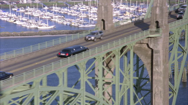 tracking shot of black stretch limo driving over yaquina bay bridge in newport, oregon. camera zooms out marinas and coast are visible. - newport oregon stock videos & royalty-free footage