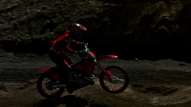 MEDIUM ANGLE OF GROUP OF DIRT BIKERS RACING ON TRACK. PANS LEFT TO RIGHT FOLLOWING BIKERS. FOCUS ON BIKER IN RED AND BLACK. BIKER MAKES A U-TURN BACK LEFT AND JUMPS OFF HILLS. PANS LEFT TO FOLLOW BIKERS JUMPING OFF HILL.