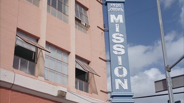 up angle of unlit neon sign that reads fred jordan mission, part of homeless shelter. neg cut. - homeless shelter stock videos and b-roll footage