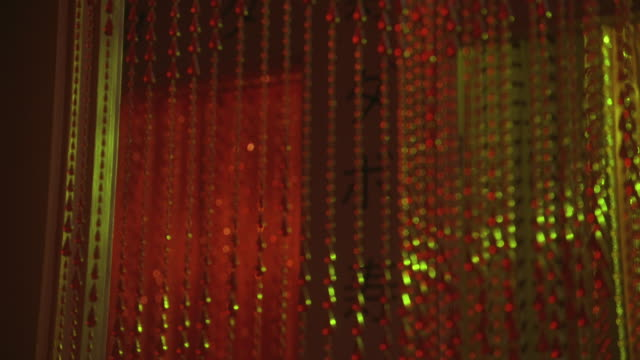 close angle on red beaded curtain hanging in doorway. hallway in background has  chinese characters on wall and is lit with pink lights. could be student apartment. lower class. - doorway stock videos and b-roll footage