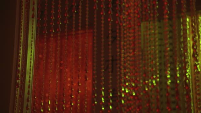 close angle on red beaded curtain hanging in doorway. hallway in background has  chinese characters on wall and is lit with pink lights. could be student apartment. lower class. - beaded curtain stock videos & royalty-free footage