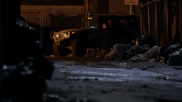medium angle of urban area alley with dozens of trash bags. hummer and military vehicles driving down alley. - hummer stock videos & royalty-free footage