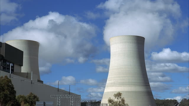 wide angle of nuclear power plant. see pair cooling towers with steam rising from top. see white and gray multi-story building to frame left. blue sky with white clouds in background. - nuclear power station stock videos & royalty-free footage