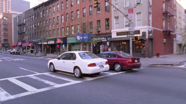 vídeos de stock e filmes b-roll de hand held moving pov driving through a street in lower manhattan neighborhood of red brick buildings.  could be chelsea, the lower east side, or greenwich village. - 2001