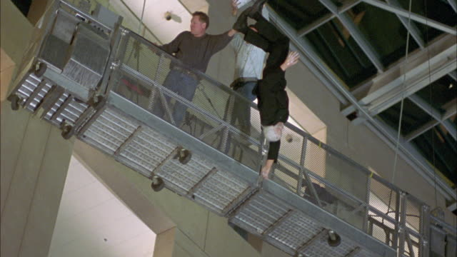 MEDIUM ANGLE OF FIGURE OR HUMAN BODY IN BLACK SUIT HANGING UPSIDE DOWN. MAN FALLS TOWARD AND HITS GROUND. BROKEN GLASS FALLS AROUND HIM. COULD BE LOBBY OF OFFICE BUILDING. SEE SMALL FOUNTAINS AND DESKS.