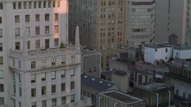 high angle down of cluster of high rise office buildings and apartment buildings. see sunlight cast on part of peach colored building. - 1995年点の映像素材/bロール