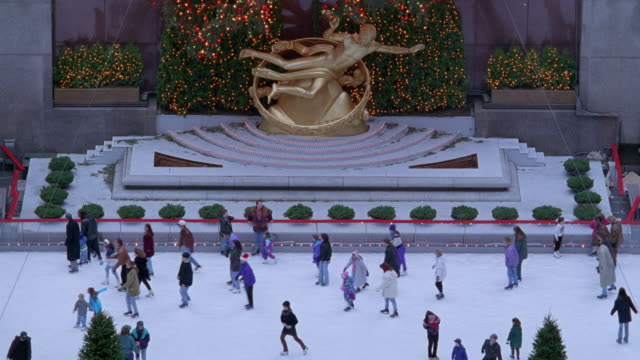 vídeos de stock, filmes e b-roll de high angle down of people ice skating on rockefeller center rink. see gold statue of angel and christmas wreath behind. - centro rockefeller