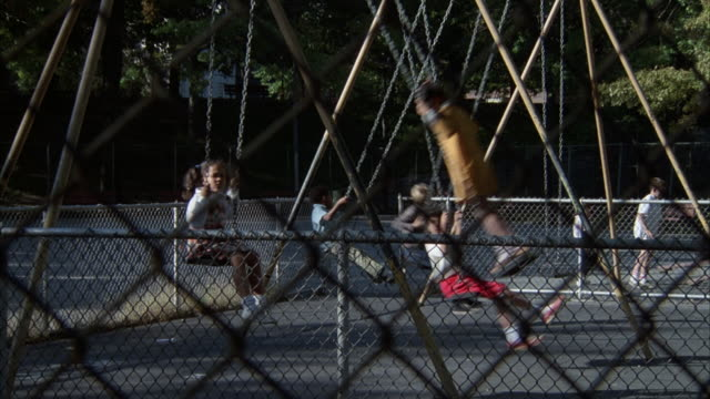 vidéos et rushes de medium angle of children playing on swings in playground. - aire de jeux