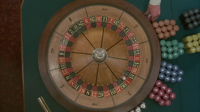 high angle down of roulette wheel, probably inside casino, with stacks of chips at right. coupier reaches in from top of frame and spins roulette wheel. ball lands on ten black. - roulette stock videos & royalty-free footage