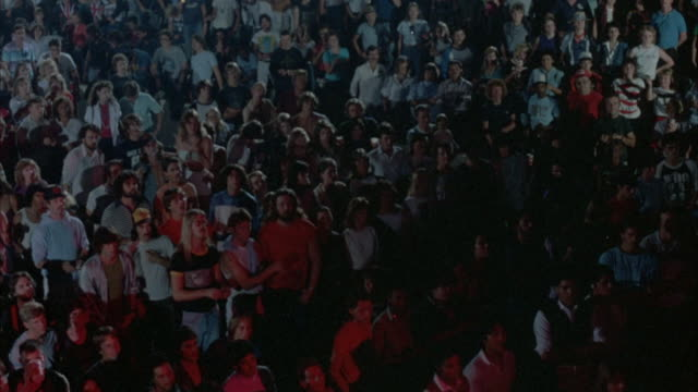 MEDIUM SHOT. YOUNG AUDIENCE IN EARLY 1980'S ATTIRE STANDS AND WATCHES ROCK CONCERT. CROWD STARTS RAISING LIGHTERS, PAN AROUND SCENE, STOP AT GROUPS OF PEOPLE DANCING WITH LIGHTERS.