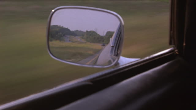 CLOSE ANGLE OF SIDE VIEW MIRROR OF CAR AS IT IS BEING CHASED BY THE POLICE. POLICE CARS WITH FLASHING BIZBARS CAN BE SEEN IN MIRROR. CAR IS DRIVING ON COUNTRY ROAD.