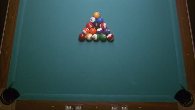 vídeos de stock e filmes b-roll de high angle down of pool table with balls set up in eight ball setup. cue ball comes from top and breaks balls. insert. - mesa de bilhar
