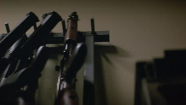 up angle of row of machine guns on rack. see hands grab machine guns off rack. camera pans left as rack empties. - rack stock videos & royalty-free footage