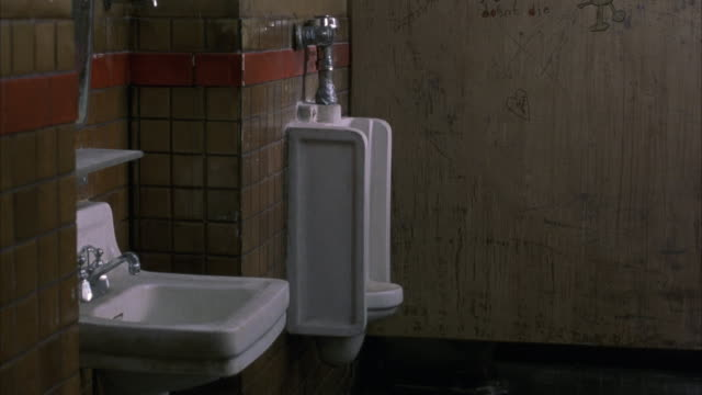 medium angle on wash sink and urinal inside gas station restroom. camera pans up on a wooden stall with various graffiti on the walls of the stall. toilets bathrooms. - urinal stock videos & royalty-free footage
