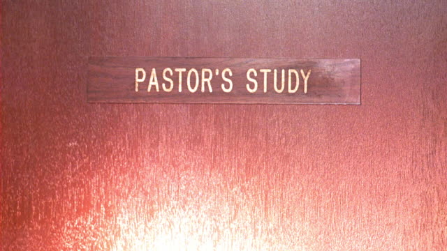 close angle of a door in the office part of a church.  pastor's study written on the door.  a flashlight beam shines on the door.  looks like a robbery or burglary burglars. - pastor stock videos & royalty-free footage