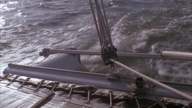 CLOSE ANGLE OF SAILBOAT HULL AND RUDDER AS IT MOVES THROUGH WATER.