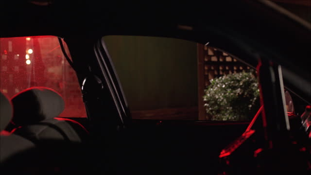 medium angle of compact car interior from front passenger pov. dashboard to right. red light filtering in through rear driver's side window. bush and screen visible in bg. - compact car stock videos and b-roll footage