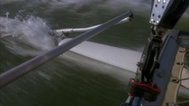 MEDIUM ANGLE OF REAR HULL AND RUDDER AS SAILBOAT MOVES THROUGH WATER.