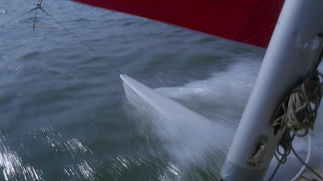 MEDIUM ANGLE OF RUDDER AS SAILBOAT MOVES THROUGH WATER. SEE PART OF RED SAIL AND MAST.
