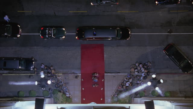 high angle down of red carpet event or premiere. spotlights and limos. crowds gathered on both sides of red carpet. - premiere stock videos & royalty-free footage