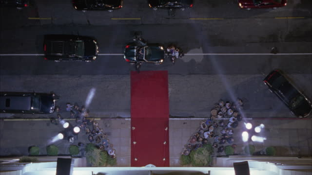 vídeos de stock, filmes e b-roll de high angle down of red carpet event or premiere. spotlights and limos. crowds gathered on both sides of red carpet. - estreia