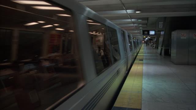 vídeos y material grabado en eventos de stock de wide angle of bart subway train in subway station. train pulls away, revealing tracks, subway platform. - bart