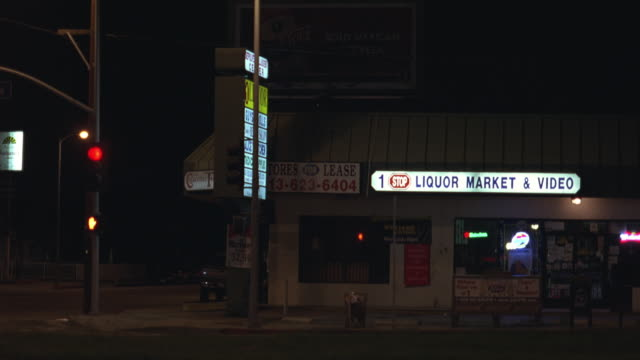 medium angle of liquor store in a strip mall near stoplight and bus stop. 1 stop liquor market and video sign lit. cars drive by. stoplight changes lights. - liquor store stock videos and b-roll footage