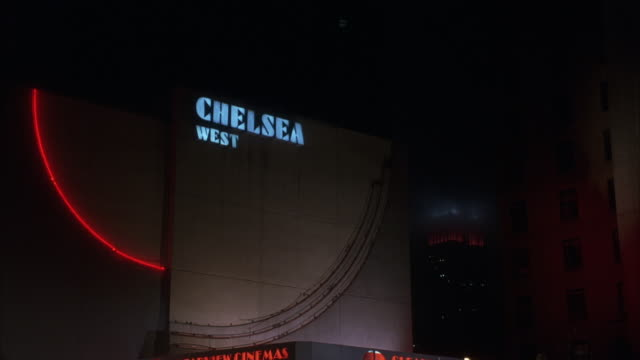 UP ANGLE ON THE CHELSEA WEST BUILDING. SEE THE EMPIRE STATE BUILDING IN BG. CAMERA PANS DOWN TO MOVIE THEATER ENTRANCE. ENTRANCE HAS MARQUEE WITH MOVIE SHOWTIME LISTINGS.