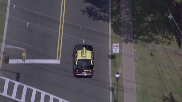 AERIAL TRACKING SHOT OF BLACK AND YELLOW TAXI DRIVING DOWN STREET THROUGH AREA BORDERED BY DENSE LINE OF TREES.