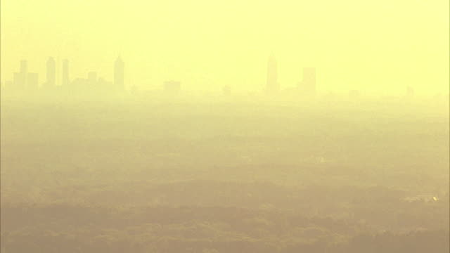 WIDE ANGLE OF CITY OF ATLANTA AS SEEN FROM HIGH VANTAGE POINT. FOREST, TREE TOPS SEEN.  YELLOW SMOG OR HAZE.