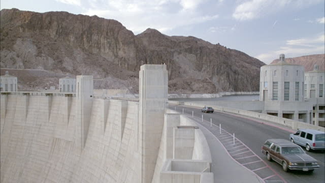 medium angle pull back of hoover dam with traffic across road. see mountains in background. - dam stock videos and b-roll footage