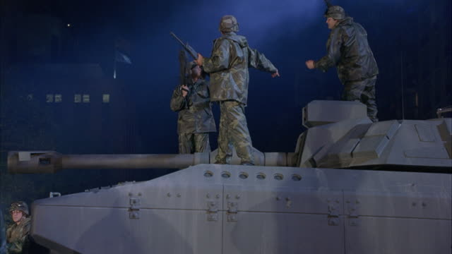 medium angle of soldiers standing by tank and some soldiers standing on top of tank. shot pans left to right to military trucks driving into military base or military camp. shot pans back and forth as each truck drives in. - military camp stock videos & royalty-free footage
