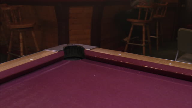 medium angle of purple pool table in bar or tavern or pool hall. cue ball and blue ball roll into corner pocket. billiards. - pool hall stock videos and b-roll footage