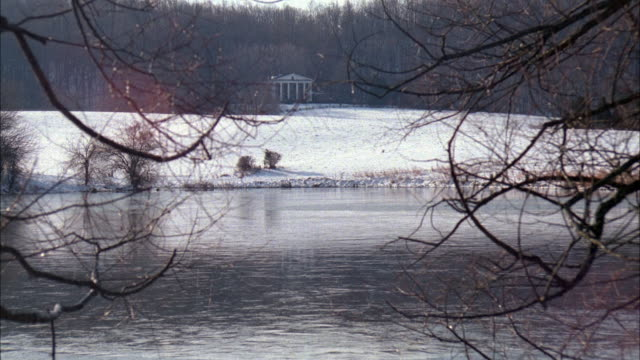 stockvideo's en b-roll-footage met medium angle establishing shot of two story mansion in background with bare tree braches in foreground. see ionic columns on house. see lake in lower foreground followed by snow covered ground leading up to house. - bare tree