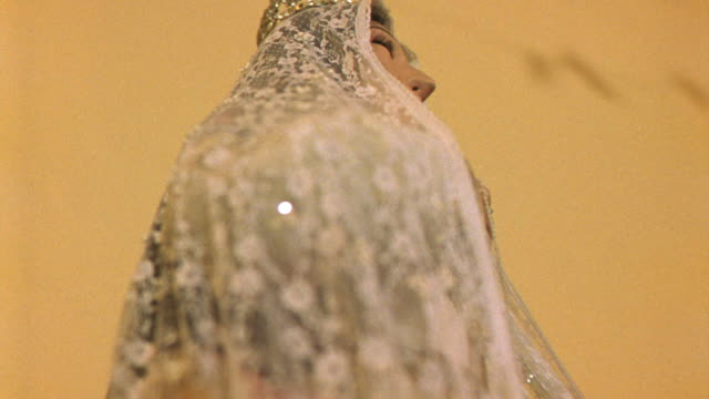 close angle of virgin mary religious statue wearing veil and crown. could be catholic church interior. could be guadalupe. camera pans right around statue. - religion stock videos & royalty-free footage