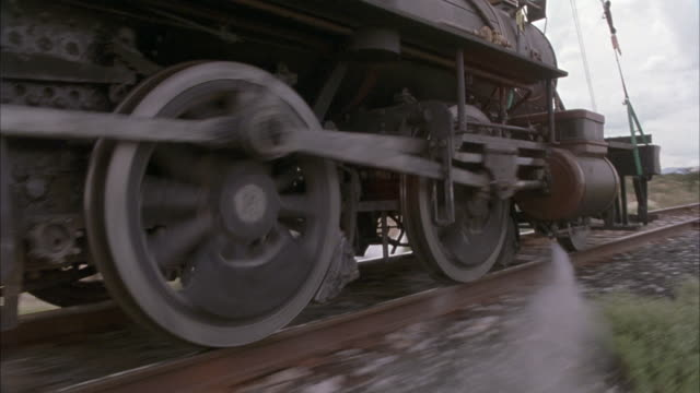 close angle of steam engine train wheels moving along railroad tracks. camera moves with train at wheel level. see steam blowing out side of train car. - wheel stock videos and b-roll footage