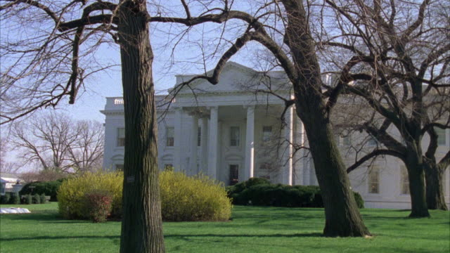 ZOOM IN ON NORTH ENTRANCE OF WHITE HOUSE, GOVERNMENT BUILDING. GRASS LAWN AND TREES WITH BARE BRANCHES.