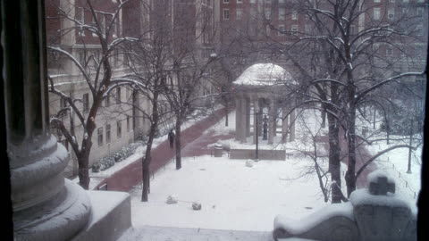 medium angle of courtyard with small stone structure in center, snow on ground, winter. at columbia university. - columbia center stock-videos und b-roll-filmmaterial
