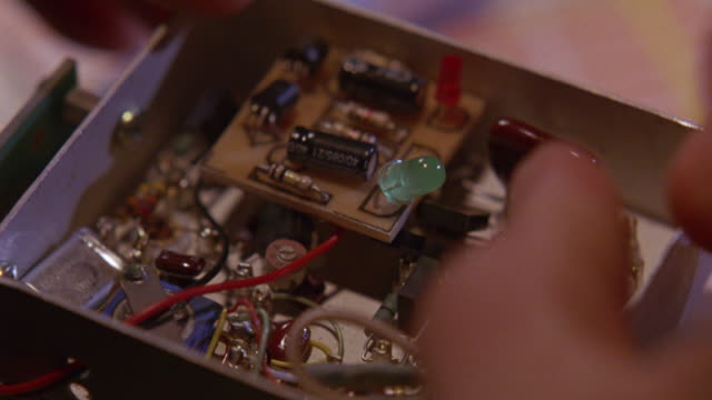 CLOSE ANGLE ON A BOX FILLED WITH ELECTRONICS.  PROBABLY THE DETONATOR FOR A BOMB OR OTHER EXPLOSIVE.  WIRES AND RESISTORS CLUTTERED TOGETHER.